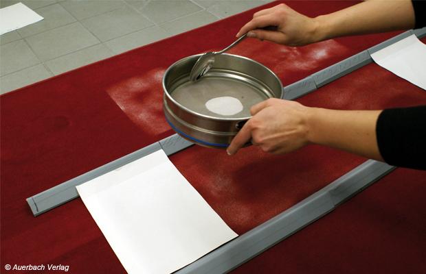 Für die Prüfung des Staubaufnahmevermögens von Teppich wird Normstaub gleichmäßig auf den Prüfteppich aufgetragen