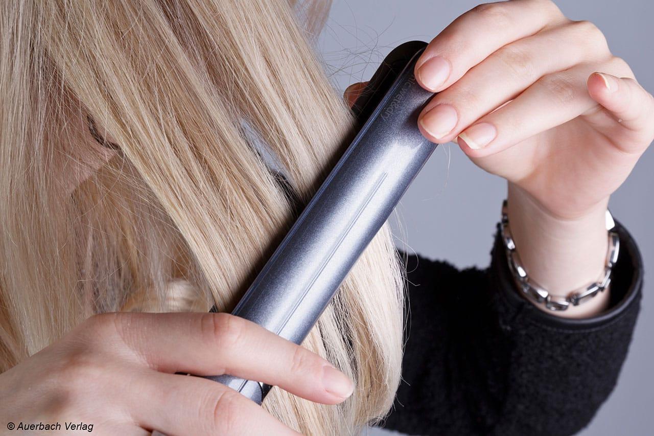 Eine Haarsträhne wird zwischen die heißen Platten geklemmt. Zügig wird das Gerät dann vom Haaransatz zu den Haarspitzen gezogen