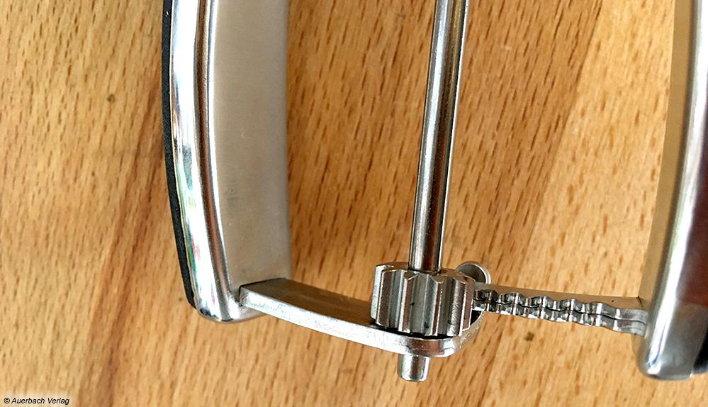 Ein Zahnrad am unteren Ende der Zange setzt ein Metallband in der Mulde in Bewegung, wodurch die Kugel abgelöst wird