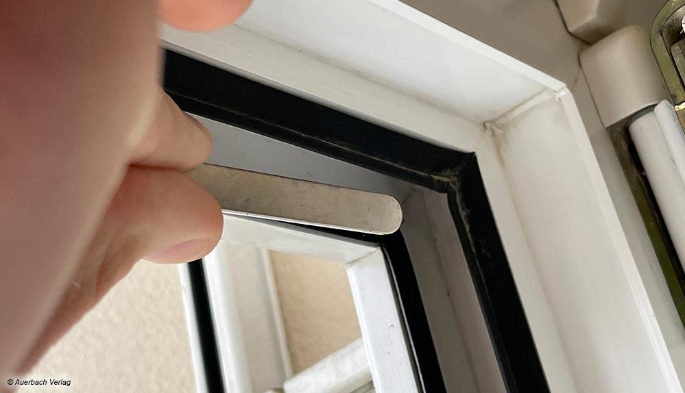 Zuerst werden selbstklebenden Metallplättchen des Fliegengitters im Fensterrahmen eingesetzt