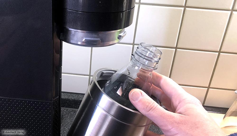 Ohne zu schrauben: Die mit Wasser gefüllte Flasche wird einfach in den Flaschenbehälter gestellt