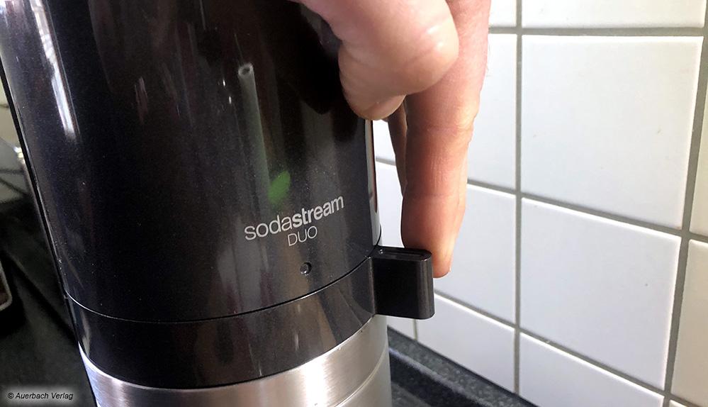 Über einen Hebel wird der Flaschenhalter mit dem Gerätekopf fest verriegelt - jetzt kann gesprudelt werden